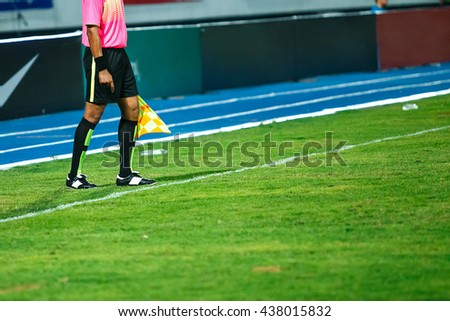 Linesman with flag standing on football yard,night time