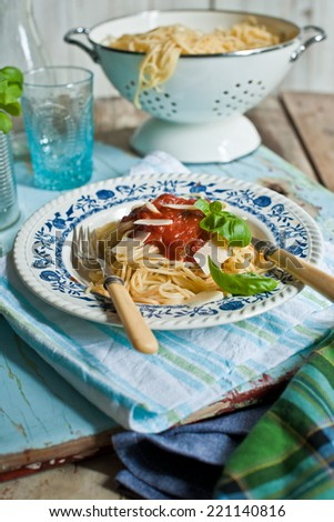 linguine pasta with a tomato bolognese beef sauce on the blue table - vintage - stock photo