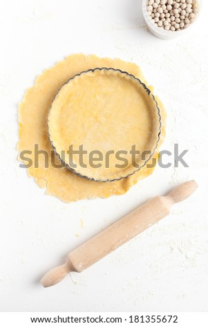 Lining a fluted tart tin with shortcrust pastry dough. Taken on a floured white surface, directly from above with rolling pin and ceramic baking beans. - stock photo