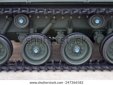 Linked metal plates and wheels of the tracks belonging to a military tank