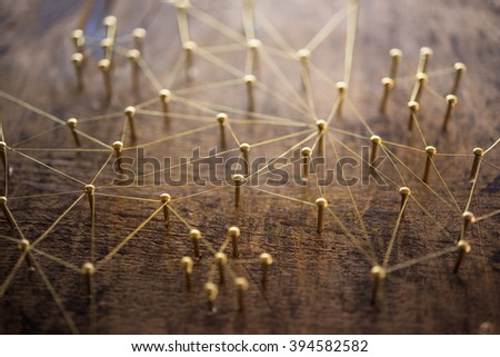 Linking entities. Network, networking, social media, internet communication abstract. Many small network connected to a larger network. Web of gold wires on rustic wood.  - stock photo