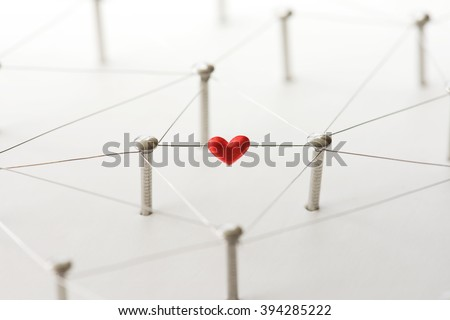 Linking entities. Network, networking, social media, internet communication abstract. Online love or matching. Web of silver wires isolated on natural white, with one connection having a red heart. - stock photo