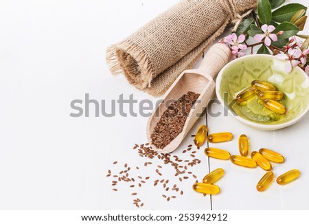 Linseed and flaxseed oil capsules over white wooden background with copy space - stock photo