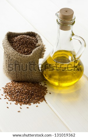 Linseed oil and flax seeds in small sack - stock photo