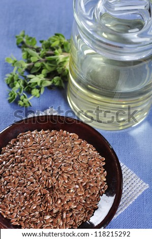 Linseed oil and flax seeds on ceramic plate closeup. Small shallow DOF - stock photo