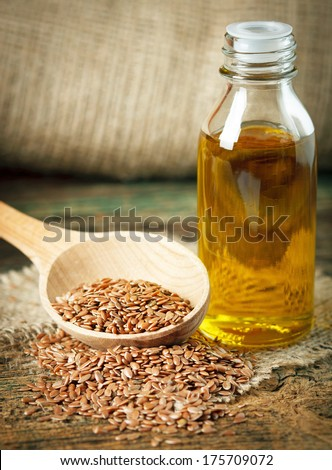 Linseed oil and flax seeds on wooden spoon - stock photo