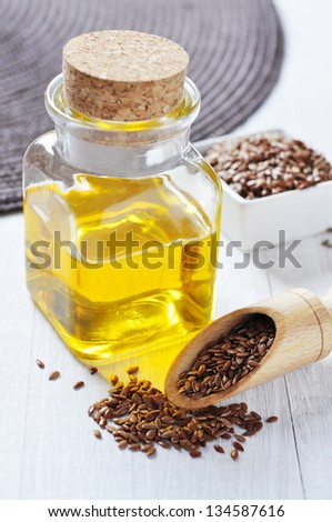 Linseed oil in a glass bottle and flax seeds on a wooden background - stock photo