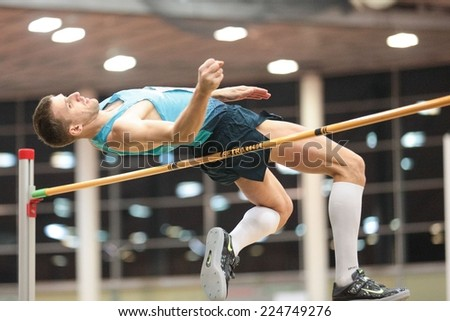 LINZ, AUSTRIA - JANUARY 30, 2014: Aleksey Dmitrik (#509 Russia) wins the men's high jump event in an indoor track and field meeting. - stock photo
