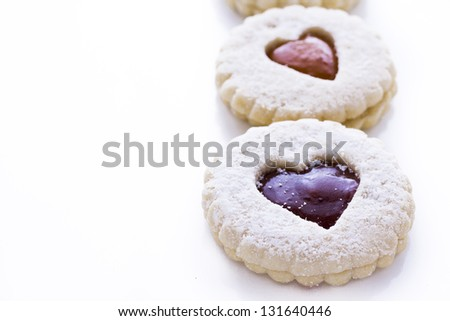 Linzer Torte cookies on white background with powdered sugar sprinkled on top.