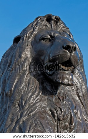 Lion at the base of Nelson's Column at Trafalgar Square in London, England (against a blue sky) - stock photo