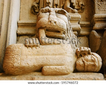 Lion devouring the sinner. Architectural detail. Facade of the church of St. Trophime in Arles. (Provence, France) - stock photo