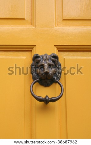 Lion Door Knocker on Bright Yellow Door - stock photo
