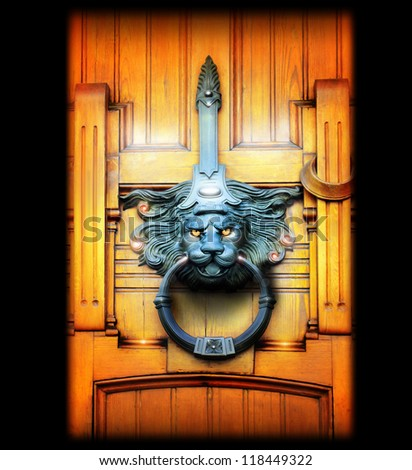 Lion doorknocker on wooden elaborately carved door with glowing eyes and lights - stock photo