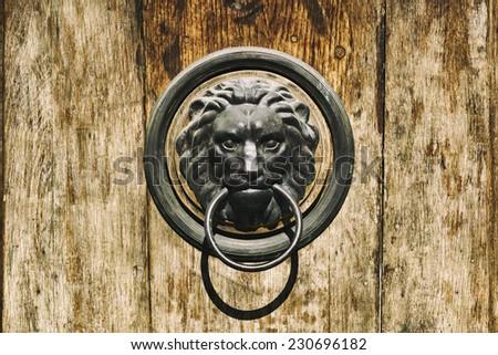 Lion head door knocker on old wooden door - stock photo