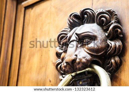 Lion head knocker on an old wooden door in Tuscany - Italy - stock photo