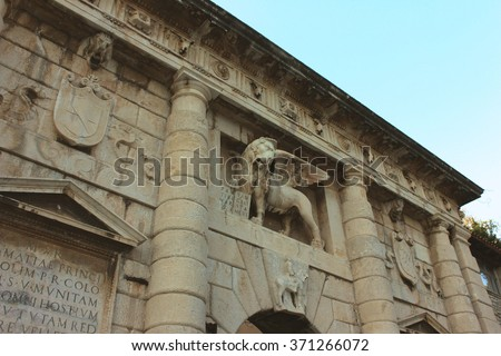 Lion of St.Mark with wings stature on the city's triumphal arch in ancient roman Adriatic town. Mediterranean architecture. Roman portico with statues, cat of arms and bas-reliefs made of limestone. - stock photo