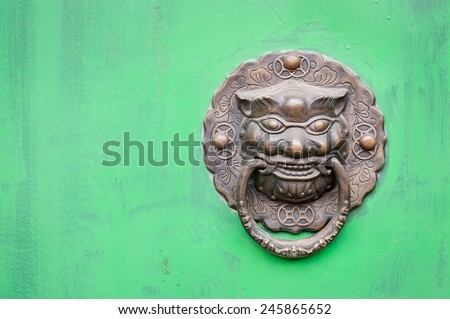 Lion-shaped door knocker against a bright green door, China