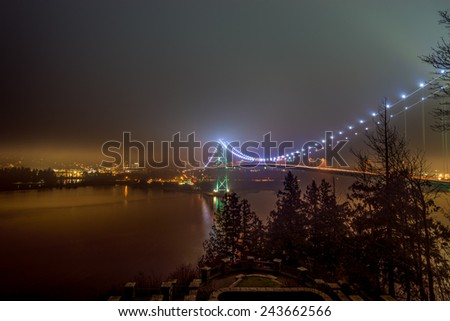 Lions Gate bridge with skyline covered in fog in Vancouver, British Columbia, Canada - stock photo