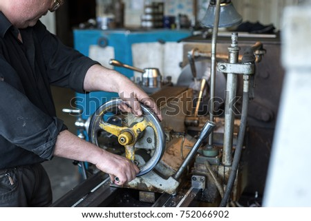 LIPETSK, RUSSIA - JUNE 15, 2017: Lipetsk Machine Tool Plant, The turner operates on a mechanical lathe. Turning works, metal processing by cutting.