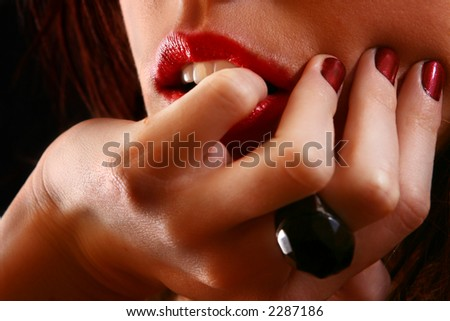 Lips and hands of a sexy female.  Close-up.  Shallow D.O.F ? only the lips and some of the fingernails are in focus. - stock photo