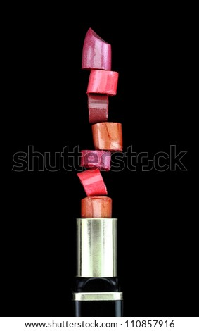 Lipstick stack on black background - stock photo