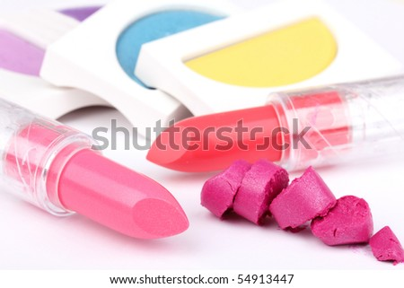 Lipsticks and eyeshadows, closed-up on white - stock photo