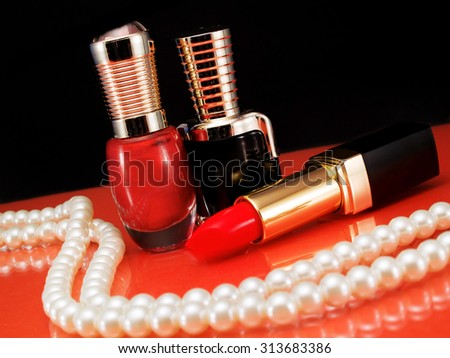 Lipsticks and nail polish bottles on red reflective background. Decorated with pearls necklace.