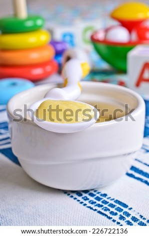 Liquid baby food yellow color on the plate on the background of toys - stock photo