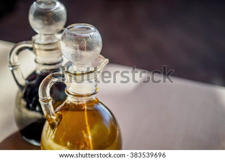 Liquid decanters on a table - one containing olive oil and the other balsamic vinegar.