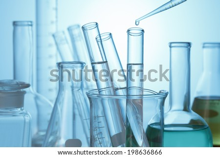 Liquid drop from laboratory glass pipette to test tube