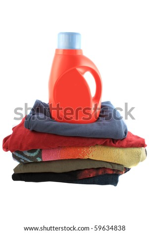 Liquid laundry detergent on top of folded pile of clothes - stock photo