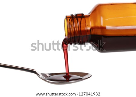 Liquid medicine pouring from a bottle on a spoon