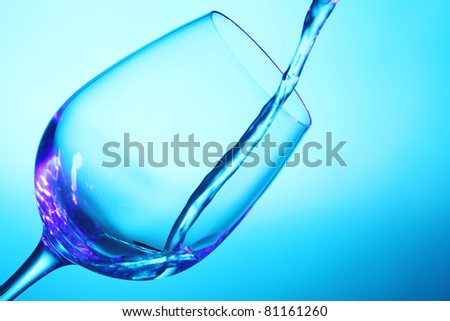 Liquid pouring into the glass in abstract multi colored light - stock photo