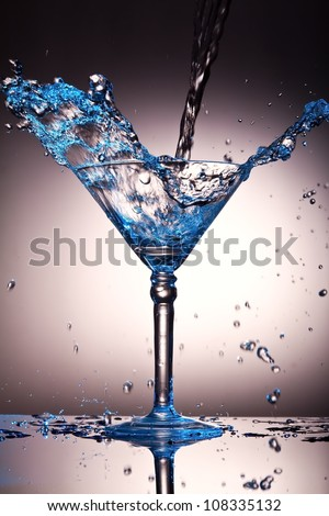 Liquid splash in a martini glass with a blue tint