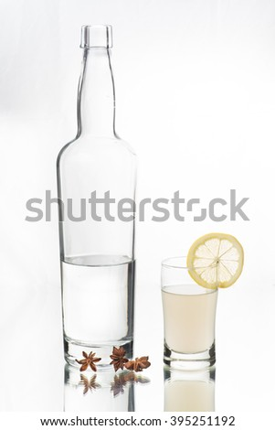 Liquor bottle and shot glass. Greek Ouzo and lemonade, Anise-flavored aperitif. on cherry wood table. Start anise on the table. Glass table top. Isolated in white background. - stock photo