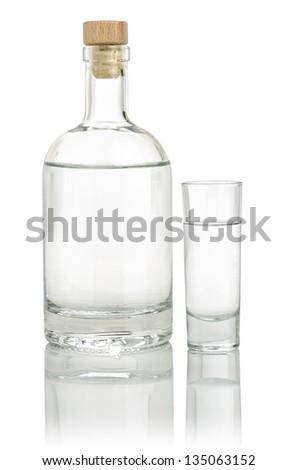 Liquor bottle with a full shot glass - stock photo