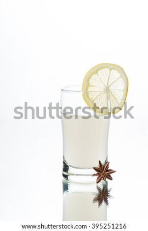Liquor shot glass filled with Greek Ouzo and lemonade, Anise-flavoured aperitif. On cherry wood table. Start anise on the table. Glass table top. Isolated in white background. - stock photo