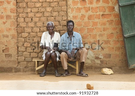 LIRA, UGANDA - JUNE 9: Two villagers wait on bus bench in Lira, Uganda on June 9, 2007. The median age in Uganda is very young at 15.1 years and population growth is only 3.576% - stock photo