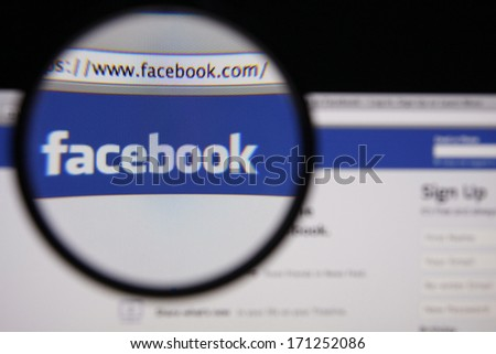 LISBON - JANUARY 14, 2014: Photo of Facebook homepage on a monitor screen through a magnifying glass. - stock photo