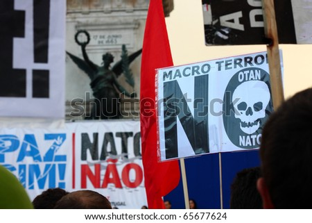 LISBON - NOVEMBER 20: Protesters hold signs with messages against NATO, as they march in the pacific demonstration promoted by anti-NATO organizations, on 20 November 2010, last day of NATO Summit in Lisbon. - stock photo