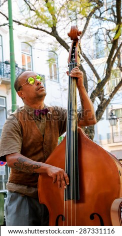 LISBON, PORTUGAL - APRIL 22, 2015: Unidentified street musician in sunglasses performs before the tourists and citizens at city square.
