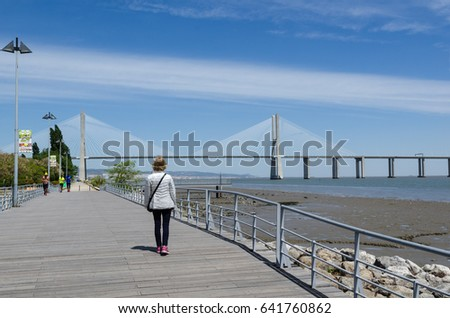 LISBON, PORTUGAL - APRIL 27: Walkway by the Tajo river and the Vasco da Gama Bridge in Lisbon, Portugal on April 27, 2017