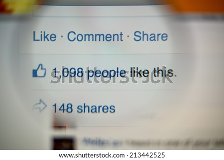 LISBON, PORTUGAL - AUGUST 27, 2014: Photo of Facebook notifications of Likes and Shares on a monitor screen through a magnifying glass.