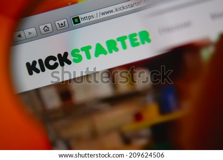 LISBON, PORTUGAL - AUGUST 3, 2014: Photo of Kickstarter homepage through a magnifying glass. Kickstarter is a crowdfunding platform. - stock photo