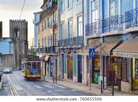 LISBON, PORTUGAL - DEC 07, 2016: Tram 28 on Alfama street. Alfama district is the Old Town of Lisbon, famous tourist attraction.
