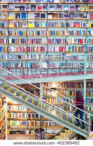 "LISBON, PORTUGAL - DEC 21, 2014: Woman on a stairs in large and famous bookstore ""Ler Devagar"" in Lisbon, Portugal - stock photo"