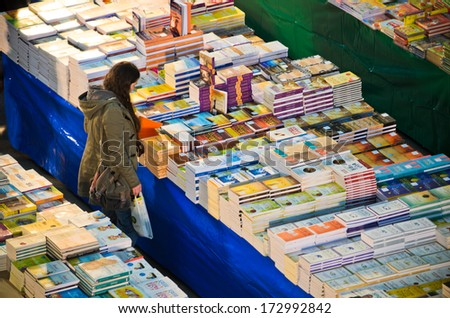 LISBON, PORTUGAL - DECEMBER 5, 2013: A woman looks at a huge stall selling books within the Oriente Railway Station in Lisbon. - stock photo