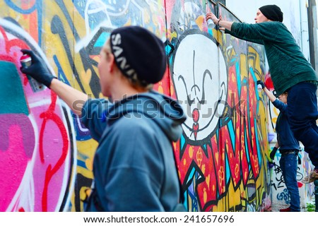 LISBON, PORTUGAL - DECEMBER 23, 2014: Boys painting graffiti on the wall in Lisbon.Along with London, Berlin, New York and others, Lisbon is one of the world's great cities for graffiti and street art - stock photo