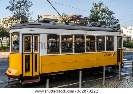 LISBON, PORTUGAL - DECEMBER 26, 2015: Famous tram 28 (Electrico 28) - vintage yellow tram goes through all over the city center, crossing many tourist attractions. - stock photo
