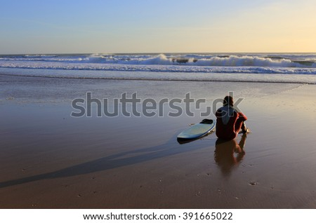 LISBON, PORTUGAL - FEBRUARY 27: An unknown surfer sits on the beach looking towards the waves and the sunset. February 27, 2016 in Lisbon, Portugal.